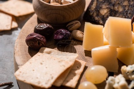 Photo for Selective focus of crackers, olives, grapes, pistachios and pieces of cheese on wooden background - Royalty Free Image