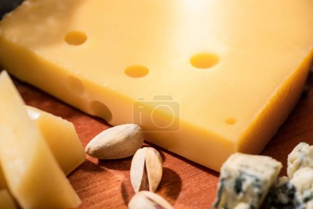 Photo for Selective focus of different kinds of cheese with pistachios on wooden background - Royalty Free Image