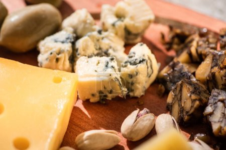 Photo for Selective focus of pieces of cheese, pistachios and olive on wooden background - Royalty Free Image