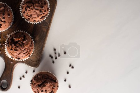 top view of fresh chocolate muffins on wooden cutting board on marble surface