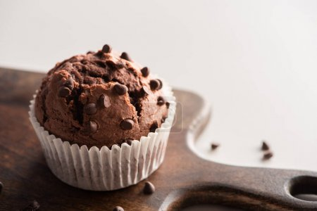 Photo for Close up view of fresh chocolate muffin on wooden cutting board - Royalty Free Image