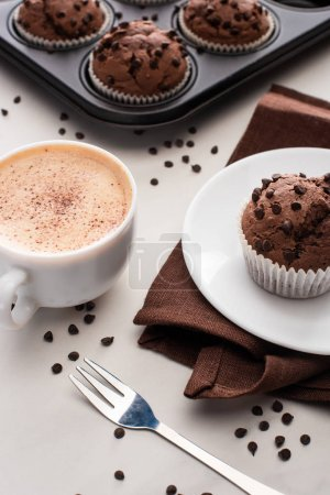 Photo for Fresh chocolate muffins in muffin tin, brown napkin with plate near coffee and fork - Royalty Free Image