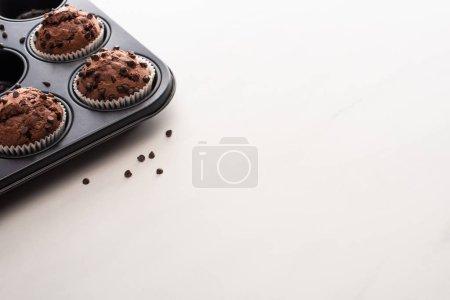 frische Schokoladenmuffins in Muffinform auf weißer Oberfläche