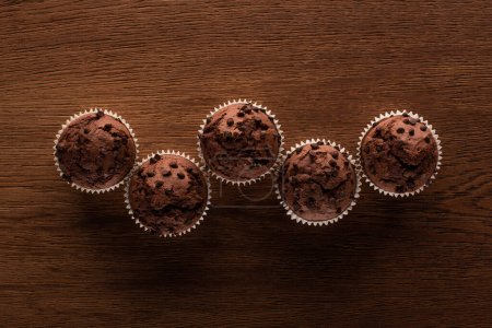 top view of fresh chocolate muffins on wooden surface