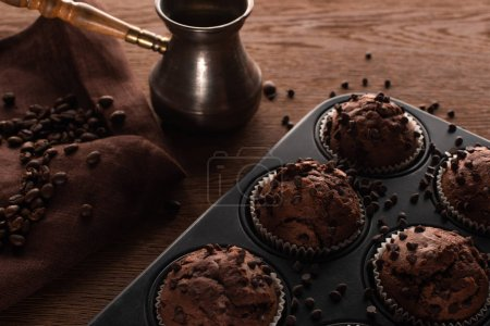 Photo for Fresh chocolate muffins in muffin tin on wooden surface near cezve with coffee beans on napkin - Royalty Free Image
