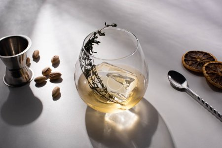 Photo pour Verre transparent avec herbe, glaçon et whisky sur table blanche avec ombre près de pistaches, cuillère, tranches d'agrumes séchées, gigue - image libre de droit