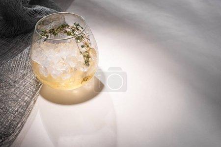 Photo pour Verre transparent avec herbe, glace et whisky sur table blanche avec ombre près du tissu - image libre de droit