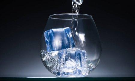 Photo pour Vodka fraîche versant dans du verre transparent avec des glaçons dans l'obscurité avec lumière arrière bleue - image libre de droit