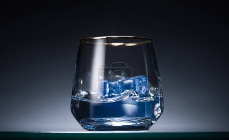 Photo for Transparent glass with ice cubes and vodka in dark with blue back light - Royalty Free Image