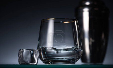 selective focus of transparent glass with vodka near ice in dark with back light and shaker