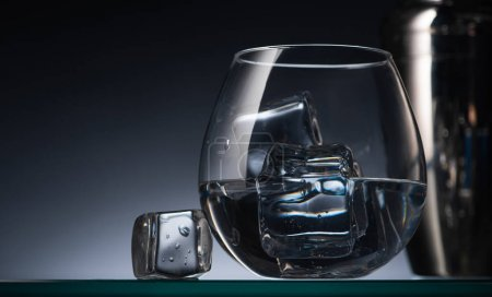 selective focus of transparent glass with ice cubes and vodka in dark with back light and shaker
