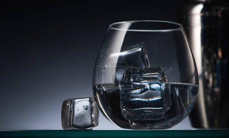 Photo for Selective focus of transparent glass with ice cubes and vodka in dark with back light and shaker - Royalty Free Image