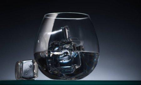 Photo pour Verre transparent avec glaçons et vodka dans l'obscurité avec contre-jour - image libre de droit