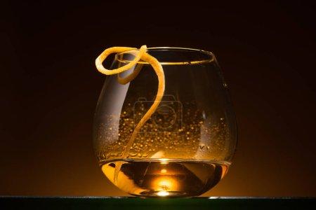 Photo pour Verre transparent avec écorce d'agrumes et vodka dans l'obscurité avec lumière arrière chaude - image libre de droit