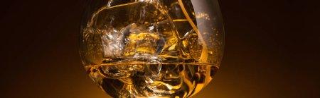Photo pour Verre transparent avec glaçons et vodka dans l'obscurité avec contre-jour chaud, vue panoramique - image libre de droit