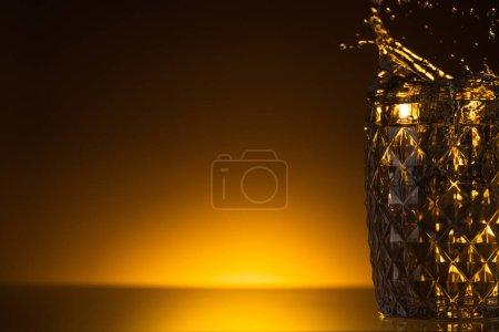 Photo pour Verre à facettes avec éclaboussures de vodka dans l'obscurité avec lumière arrière chaude - image libre de droit