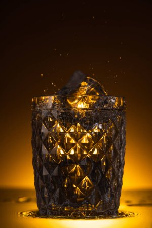 Photo for Faceted glass with ice cube and splashing vodka in dark with warm back light - Royalty Free Image