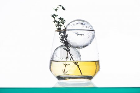 transparent glass with golden liquid, herb and round ice isolated on white