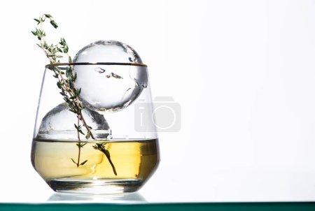 Foto de Vidrio transparente con líquido dorado, hierba y hielo redondo aislado en blanco - Imagen libre de derechos