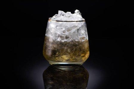 Photo pour Verre transparent avec glace et liquide doré sur fond noir - image libre de droit