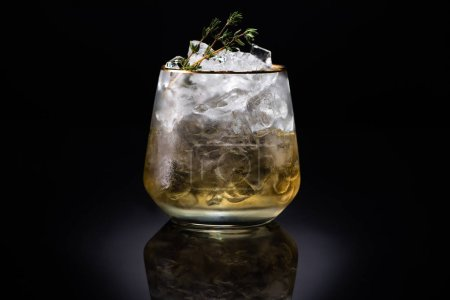 transparent glass with ice and golden liquid garnished with herb on black background