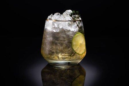 Photo pour Verre transparent avec glace et liquide doré garni d'herbe et de chaux sur fond noir - image libre de droit