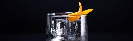 Photo pour Verre transparent avec glaçon et vodka garni d'une pelure d'orange isolé sur une pelure noire panoramique - image libre de droit