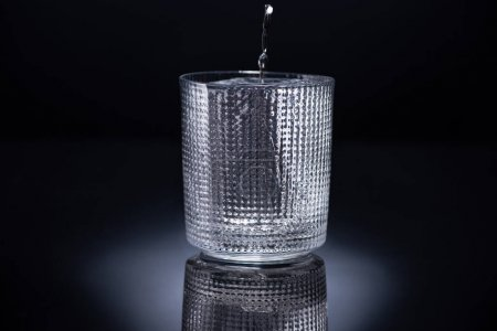 Photo for Faceted glass with ice and pouring vodka on black background - Royalty Free Image