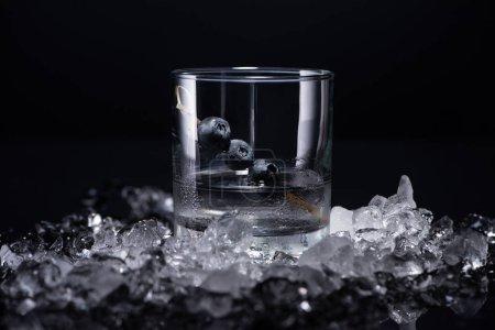Photo pour Verre transparent avec vodka et bleuets près de glace fracassée isolé sur noir - image libre de droit