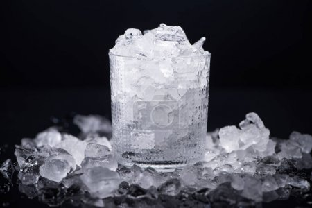 Photo for Transparent glass filled with smashed ice isolated on black - Royalty Free Image