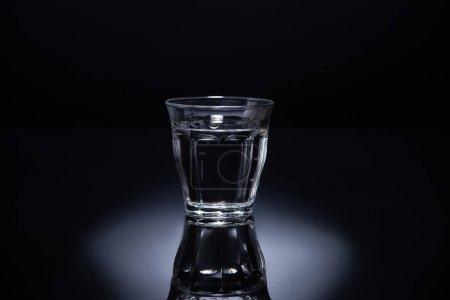 Photo pour Verre transparent avec liquide sur fond noir - image libre de droit