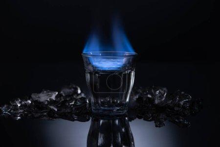 transparent glass with burning liquid near ice on black background