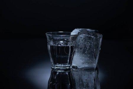 Photo pour Verre transparent avec glaçon et vodka sur fond noir - image libre de droit