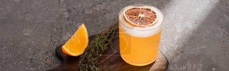 Photo pour Cocktail à l'orange et aux herbes sur planche à découper en bois sur surface béton, panoramique - image libre de droit