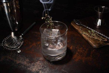Photo pour Verre transparent avec herbe brûlante, glaçon et vodka sur la surface altérée - image libre de droit