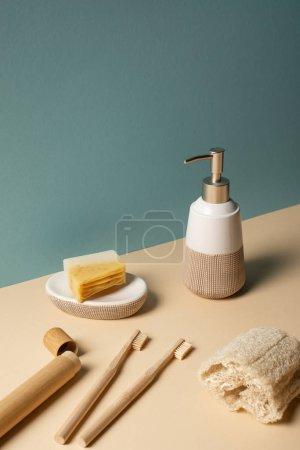 Foto de Toothbrushes, toothbrush case with dispenser, sponge and soap dish on beige and grey, zero waste concept - Imagen libre de derechos