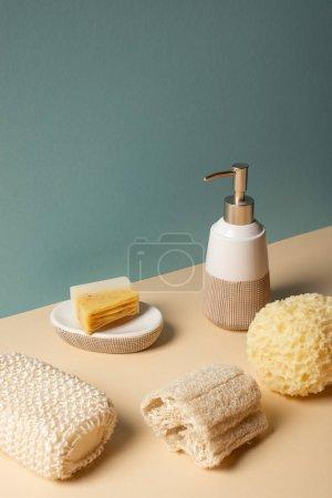 Foto de Sponges with liquid soap dispenser and soap dish on beige and grey, zero waste concept - Imagen libre de derechos