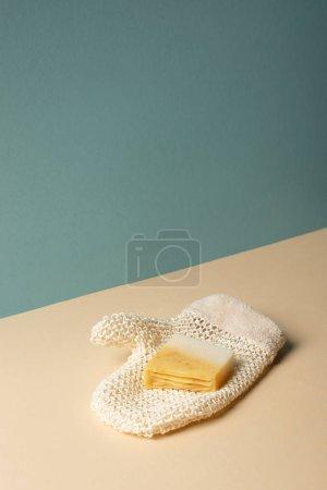 Foto de Bath glove with soap on beige and grey, zero waste concept - Imagen libre de derechos