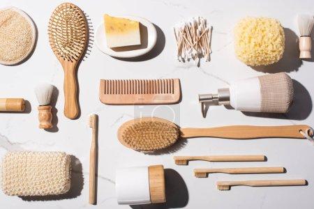 Foto de Vista superior de comb, bastones de oreja, esponjas, cepillos de pelo, dispensador de jabón líquido, cepillos de afeitar, cepillos dentados sobre fondo blanco, concepto de residuo cero. - Imagen libre de derechos