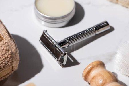 Photo pour Concentration sélective de rasoir, serviette, pot de lavage, brosses à raser sur fond blanc, concept zéro déchet - image libre de droit