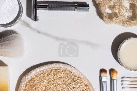 Foto de Top view of cosmetic brushes, razor, sponges, soap, ear sticks, jar of wax on white background, zero waste concept - Imagen libre de derechos