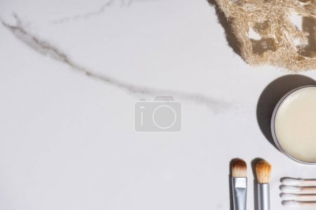 Top view of cosmetic brushes, sponge, jar of wax and ear sticks on white background, zero waste concept
