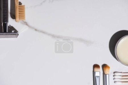 Foto de Vista superior de cepillos cosméticos, cepillos de dientes, rasguños, jarros de cera y bastones de oreja sobre fondo blanco, concepto de residuo cero. - Imagen libre de derechos