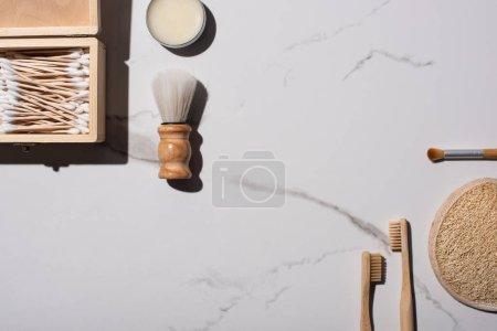 Widok z góry na szczoteczki do golenia i kosmetyczne, szczoteczki do zębów, słoik wosku, pudełko pałeczek do uszu, gąbka na białym tle, koncepcja zero odpadów