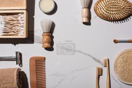 Photo pour Vue du dessus des brosses à raser et cosmétiques, peigne, serviette, brosses à dents, cire, boîte de bâtons d'oreille, éponge, serviette sur fond blanc, concept zéro déchet - image libre de droit