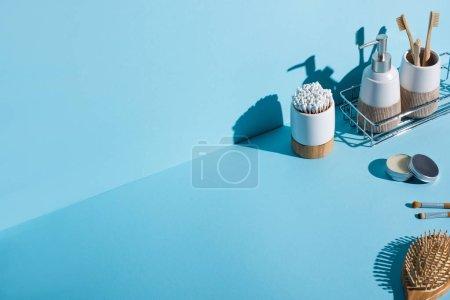 Photo pour Porte-brosses à dents avec brosses à dents et bâtons d'oreille, distributeur sur étagère de salle de bain, brosses cosmétiques, brosse à cheveux sur fond bleu, concept zéro déchet - image libre de droit