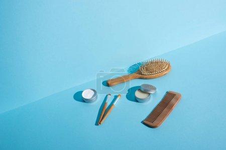 Foto de Cepillo de pelo, peine, jarras de cera y polvo de dientes, cepillos cosméticos en fondo azul, concepto de residuo cero. - Imagen libre de derechos