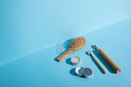 Foto de Cepillo de pelo, jarras de cera y polvo de dientes, cepillos de dientes en fondo azul, concepto de residuo cero. - Imagen libre de derechos