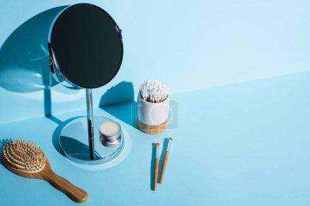 Photo pour Miroir avec pot de cire à côté de la brosse à cheveux, brosses cosmétiques, porte-brosse à dents avec bâtonnets d'oreilles sur fond bleu, concept zéro déchet - image libre de droit