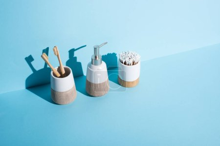 Foto de Toothbrush holders with ear sticks and toothbrushes with dispenser liquid soap on blue background, zero waste concept - Imagen libre de derechos